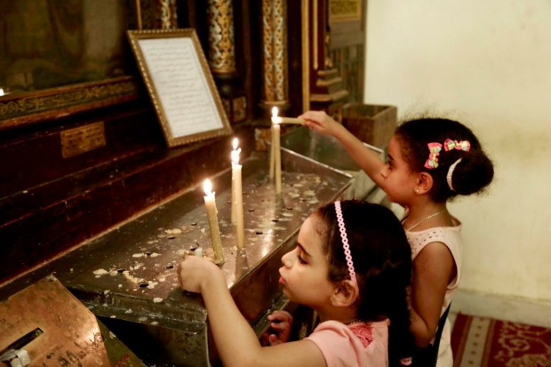Egyptian Christian girls light candles in the Hanging Church in Old Cairo, Egypt, Tuesday, Aug. 30, 2016. (AP Photo/Nariman El-Mofty)